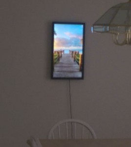 Digital art display on my dining room wall, showing a wooden walkway leading to a beach.