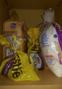 Flour, sugar, and two half-empty bags of chocolate chips on a shelf.