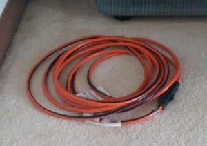 Orange electrical cord on the carpet next to the couch.