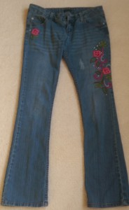Blue jeans with embroidered flowers and leaves.