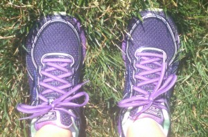 Purple running shoes in grass.