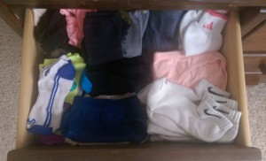 Wooden drawer stacked high with socks of many kinds.