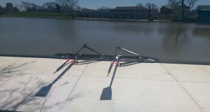 Black double scull in the river, next to a white dock.