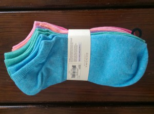 Pack of new socks in assorted pastel colors, on top of my dresser.