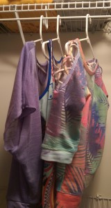 Three pretty new tops in purple and other spring colors, hanging in my closet.