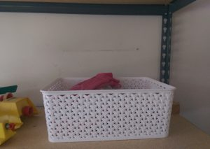 White plastic lattice-weave basket on garage shelf.