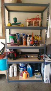 Particle board garage shelves in a metal frame.