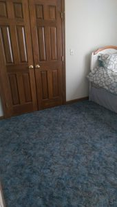 Blue carpet, just vacuumed, with closet doors and a corner of a bed in the background.