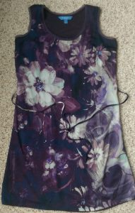 Dark purple sleeveless dress with white floral pattern.