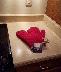 Pair of red oven mitts on the kitchen counter.