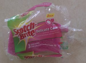 "One sponge in an open pack of three Scotch-Brite ""Delicate Care"" scrub sponges."