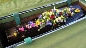 Casket covered in flowers.