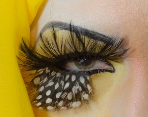 Eye decorated to resemble a bird's head.