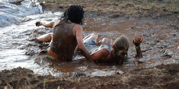 Mud wrestling in an outdoor pit.