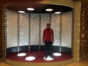 Person in a Star Trek uniform standing on a transporter.