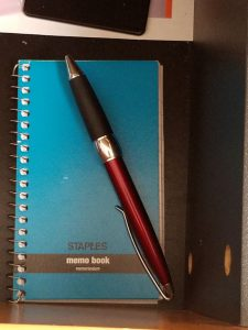 Small spiral notepad in desk drawer with pen.