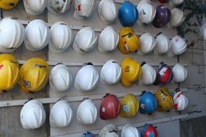 Rows of hard hats hanging on a wall.
