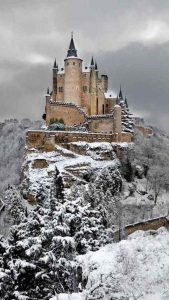 Alcázar of Segovia on a dark, snowy winter day.