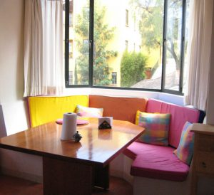 Sunny breakfast nook with brightly colored cushions on a bench.