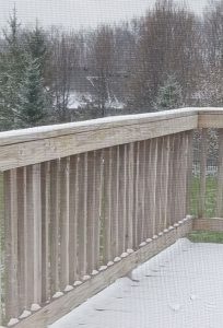 Snow on my deck in April, with trees still bare.
