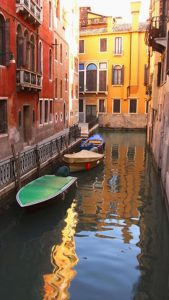 Brightly colored image of boats docked in a canal between buildings.