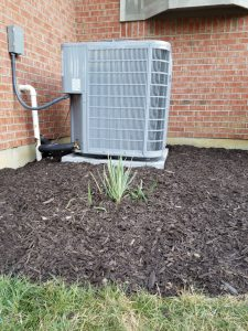 New air conditioner with fresh mulch around it.