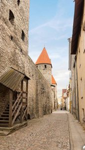 Narrow cobblestone street between stone and wood buildings.