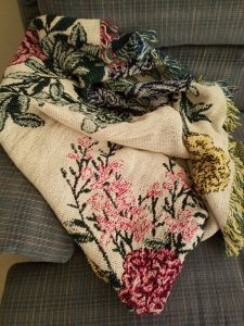Blanket with floral pattern on couch.