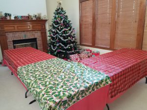 Tables pushed together, with holiday tablecloths, around the Christmas tree.
