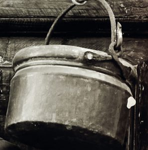 Old pot hanging on a hook.