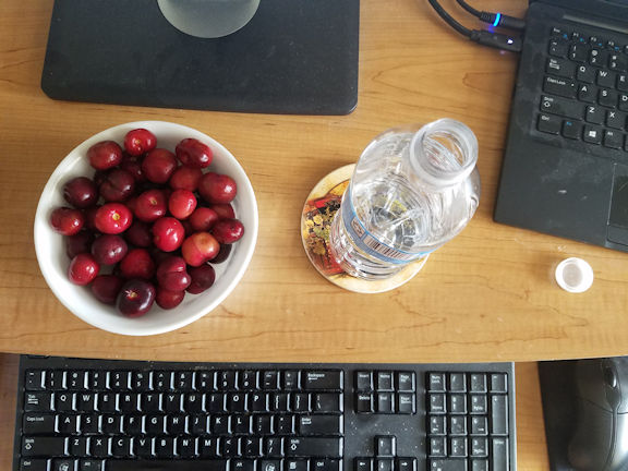 A bowl of cherries and a plastic water bottle on a desk with a computer.