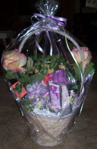 Photo of gift basket wrapped in plastic with purple ribbons.