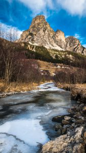 Photo of a frozen stream with bare mountains in the background.