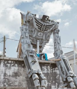 Large robot leaning over a wall.