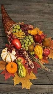 Thanksgiving cornucopia with harvest fruits and autumn leaves.