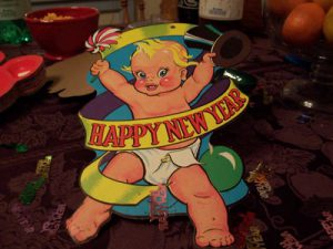 Cartoon image of a baby with a Happy New Year sash.
