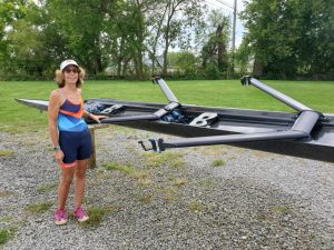 Meg standing next to a double scull on slings.
