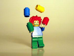 A Lego person juggling Lego pieces.